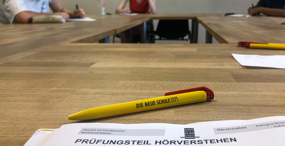 On a table is a German exam Europa Zertifikat with a pen from DIE NEUE SCHULE Berlin