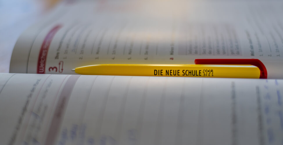 A pen from DIE NEUE SCHULE Berlin lies in a German course Book on educational leave