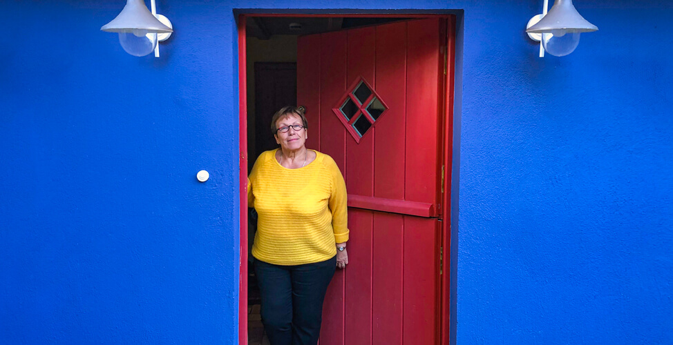A friendly hostess of DIE NEUE SCHULE Berlin stands in the open door of a blue accommodation